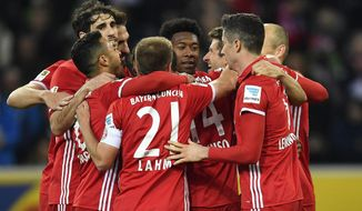 Players celebrate Bayern's Thomas Mueller, center, after he scored the opening goal during the German Bundesliga soccer match between Borussia Moenchengladbach and Bayern Munich in Moenchengladbach, Germany, Sunday, March 19, 2017. (AP Photo/Martin Meissner)
