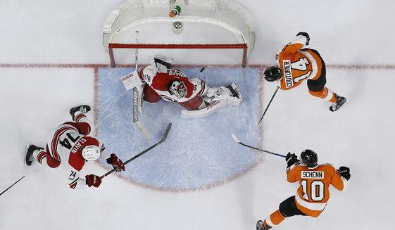 Philadelphia Flyers' Brayden Schenn (10) scores past Carolina Hurricanes' Cam Ward (30) as Sean Couturier (14) and Jaccob Slavin (74) watch during overtime of an NHL hockey game, Sunday, March 19, 2017, in Philadelphia. Philadelphia won 4-3. (AP Photo/Matt Slocum)