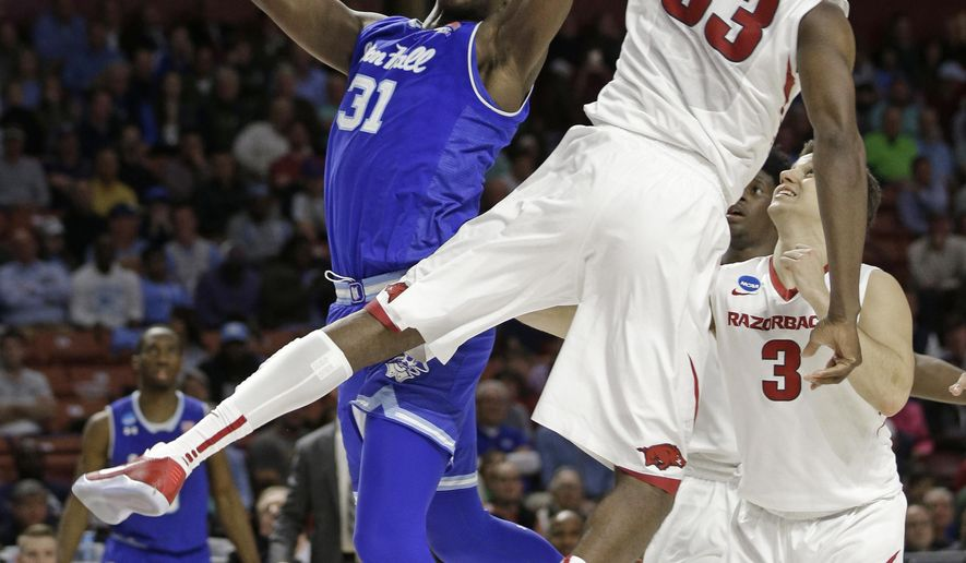 Seton Hall's Angel Delgado (31) shoots over Arkansas's Moses Kingsley (33) during the second half in a first-round game of the NCAA men's college basketball tournament in Greenville, S.C., Friday, March 17, 2017. (AP Photo/Chuck Burton)