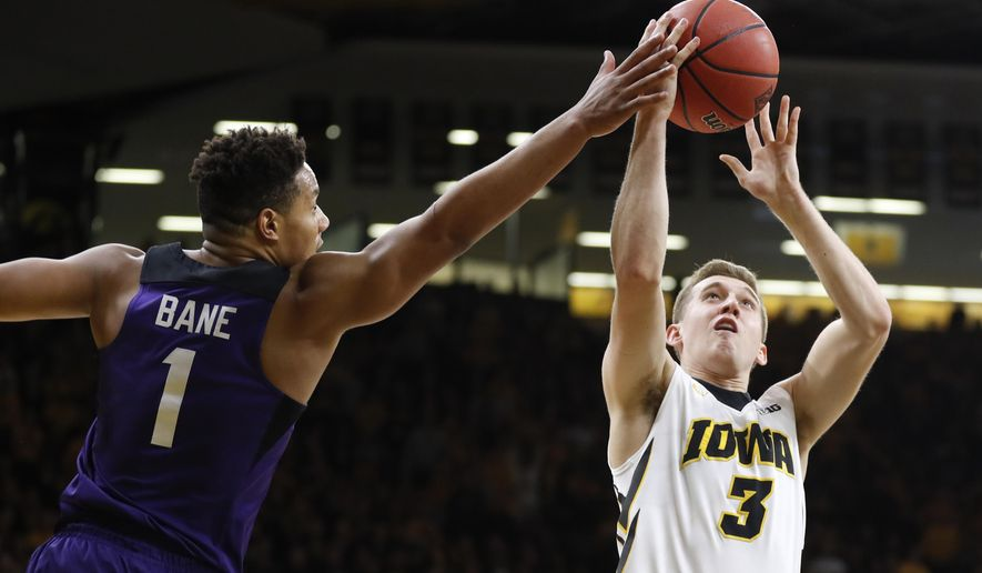 TCU guard Desmond Bane (1) tries to block a shot by Iowa guard Jordan Bohannon (3) during the second half of a second-round game in the NIT college basketball tournament, Sunday, March 19, 2017, in Iowa City, Iowa. TCU won 94-92. (AP Photo/Charlie Neibergall)