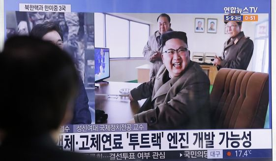 "A man watches a TV news program showing an image, published in North Korea's Rodong Sinmun newspaper, of North Korean leader Kim Jong Un at the country's Sohae launch site, at Seoul Railway station in Seoul, South Korea, Sunday, March 19, 2017. North Korea has conducted a ground test of a new type of high-thrust rocket engine that leader Kim Jong Un is calling a revolutionary breakthrough for the country's space program. The letters read "" New type engine."" (AP Photo/Ahn Young-joon)"