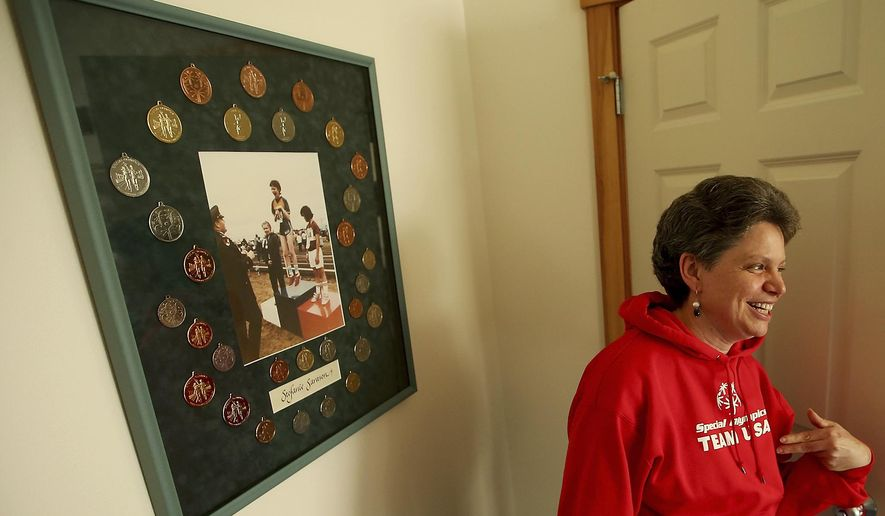 In this Friday, March 10, 2017 photo, Stefanie Sarason smiles as she talks about the photo surrounded by medals behind her that was published in the Seattle Times in 1985 and depicts her jumping on the first place podium before receiving her gold medal, at her Bainbridge Island, Wash., home. Sarason is heading to the Special Olympics World Games in Austria. (Meegan M. Reid/Kitsap Sun via AP)