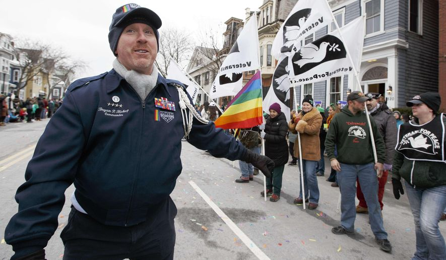 OutVets founder Bryan Bishop walks past a group from Veterans for Peace during the annual St. Patrick's Day parade in Boston, Sunday, March 19, 2017. The parade's organizer, the South Boston Allied War Council, initially banned OutVets from this year's parade, saying it failed to comply with guidelines by carrying the rainbow banner last year. (AP Photo/Michael Dwyer)