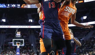 Detroit Pistons forward Marcus Morris (13) drives on Phoenix Suns forward Derrick Jones Jr. (10) during the first half of an NBA basketball game in Auburn Hills, Mich., Sunday, March 19, 2017. (AP Photo/Paul Sancya)
