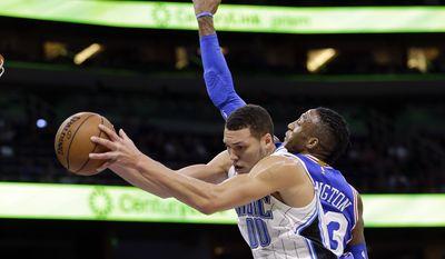 Orlando Magic's Aaron Gordon grabs a rebound away from Philadelphia 76ers' Robert Covington during the first half of an NBA basketball game, Monday, March 20, 2017, in Orlando, Fla. (AP Photo/John Raoux)