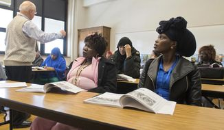 ADVANCE FOR SATURDAY MARCH 25 AND THEREAFTER - In a March 15, 2017 photo, Mary Buak, right, and Nyawargak Jack, center, listen to teacher Tom Tacheny during a citizenship class at Lincoln Community Center in Mankato, Minn. Citizenship classes at the center and elsewhere in Mankato have had slightly higher enrollments this year, an occurrence that roughly coincides with the initial travel ban implemented by President Donald Trump in January. (Jackson Forderer/The Free Press via AP)