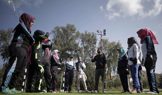 In this Sunday, March 19, 2017 photo, Palestinian coach, Mahmoud Tafesh, gives instructions before starting training for an all women's baseball game, on a soccer field in Khan Younis, southern Gaza Strip. The female players wear hijabs, not helmets, toss around tennis balls, not baseballs and their leather gloves have been replaced by black imitations knitted from fabric. The group of young women are trying to bring baseball to Gaza -- giving the traditional American pastime a distinctly local feel. (AP Photo/Khalil Hamra)