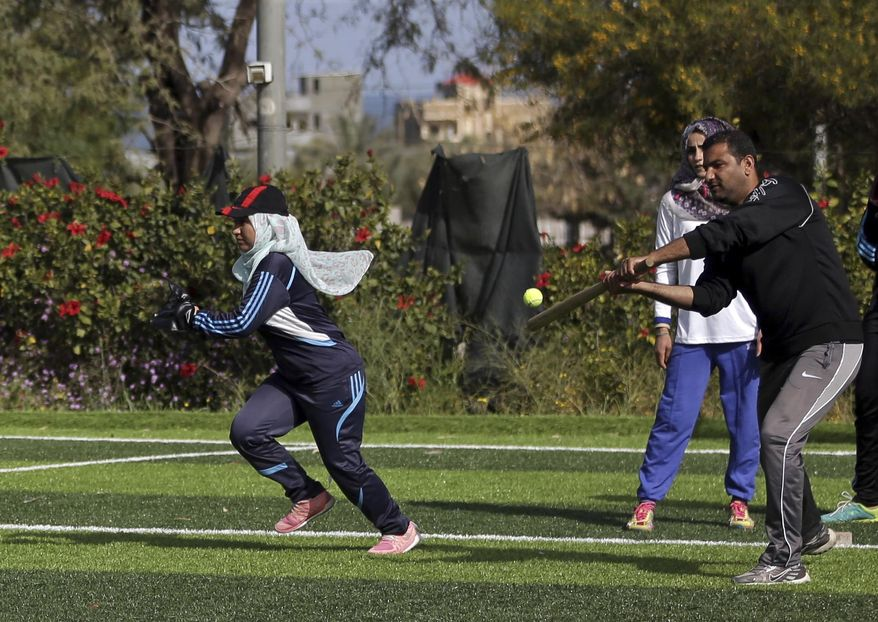In this Sunday, March 19, 2017 photo, Palestinian women train for an all women's baseball game, on a soccer field, in Khan Younis, southern Gaza Strip. The female players wear hijabs, not helmets, toss around tennis balls, not baseballs and their leather gloves have been replaced by black imitations knitted from fabric. The group of young women are trying to bring baseball to Gaza -- giving the traditional American pastime a distinctly local feel. (AP Photo/Khalil Hamra)