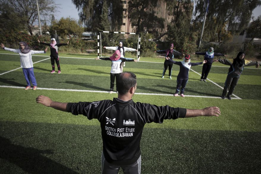 In this Sunday, March 19, 2017 photo, Palestinian coach, Mahmoud Tafesh, leads warm up exercises before an all women's baseball game, on a soccer field in Khan Younis, southern Gaza Strip. The female players wear hijabs, not helmets, toss around tennis balls, not baseballs and their leather gloves have been replaced by black imitations knitted from fabric. The group of young women is trying to bring baseball to Gaza -- giving the traditional American pastime a distinctly local feel (AP Photo/Khalil Hamra)