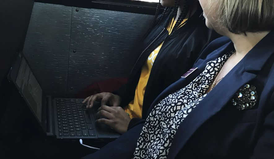 St. Stephen Middle School student Lakaysha Governor works on her Chromebook on Monday, March 20, 2017, on a school bus recently outfitted with WiFi by tech giant Google, as College of Charleston professor RoxAnn Stalvey looks on in St. Stephen, S.C. Lakysha is one of nearly 2,000 students in South Carolina's rural Berkeley County benefiting from a grant from Google, which on Monday unveiled one of its  WiFi-equipped school buses in the area. (AP Photo/Meg Kinnard)
