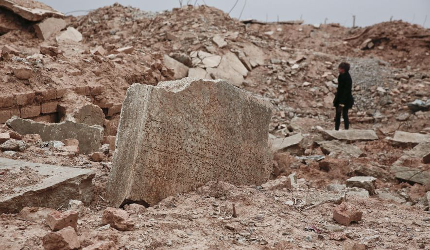 FILE - In this Wednesday, Dec. 14, 2016 file photo, a stone tablet with cuneiform writing in the foreground as UNESCO's Iraq representative Louise Haxthausen documents the damage wreaked by the Islamic State group at the ancient site of Nimrud, Iraq. France is trying to raise tens of millions of dollars from international donors who gathered Monday March 20, 2017, to protect cultural heritage sites threatened by war and the kind of destruction carried out by Islamic State militants. (AP Photo/Maya Alleruzzo, File)