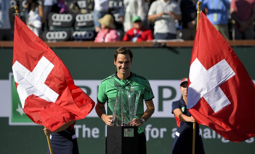 Roger Federer, of Switzerland, poses with the trophy after his win against Stanislas Wawrinka, of Switzerland, in the finals of the BNP Paribas Open tennis tournament, Sunday, March 19, 2017, in Indian Wells, Calif. (AP Photo/Mark J. Terrill)