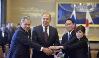 Russian Foreign Minister Sergei Lavrov, second left, Russian Defense Minister Sergei Shoigu, left, put hands together with Japanese Foreign Minister Fumio Kishida, second right, and Japanese Defense Minister Tomomi Inada during the two-plus-two meeting in Tokyo Monday, March 20, 2017. The foreign and defense ministers from Japan and Russia met in Tokyo on Monday, with both sides expressing hope that discussions on joint development of islands claimed by both countries might help them move closer to resolving the territorial dispute preventing them from forging a peace treaty. (David Mareuil/Pool Photo via AP)