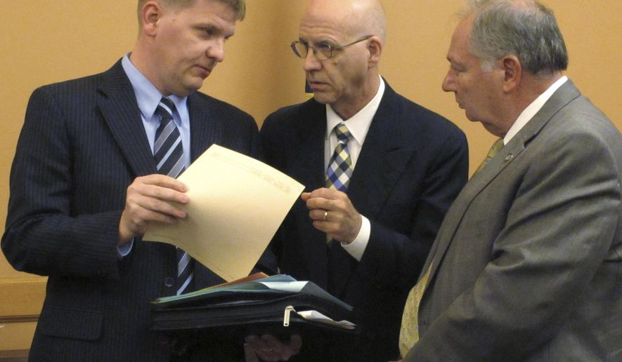 Shawn Sullivan, left, Kansas Gov. Sam Brownback's budget director, confers with J.G. Scott, center, the chief fiscal analyst for the Kansas Legislature's research staff, and Senate Majority Leader Jim Denning, R-Overland Park, right, following a meeting of the Senate Ways and Means Committee, Monday, March 20, 2017, at the Statehouse in Topeka, Kan. The committee is proposing a two percent pay raise for most state workers. (AP Photo/John Hanna)