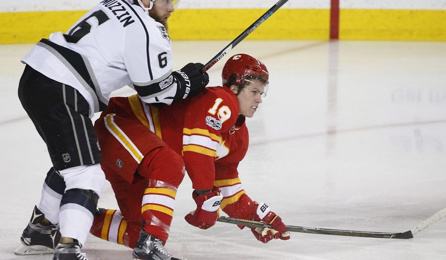 Calgary Flames' Matthew Tkachuk, right, is knocked down by Los Angeles Kings' Jake Muzzin during the first period of an NHL hockey game in Calgary, Alberta, Sunday, March 19, 2017. (Larry MacDougal/The Canadian Press via AP)