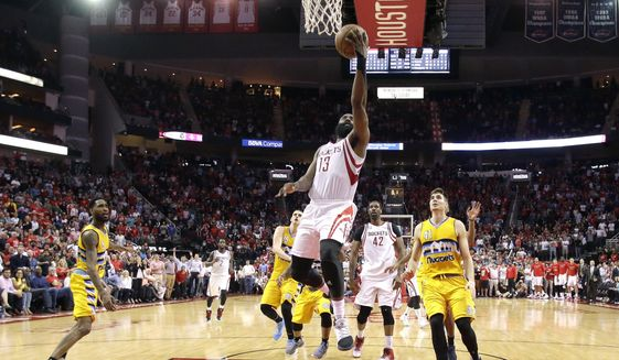 Houston Rockets' James Harden (13) goes up to score the game-winning basket against the Denver Nuggets during the second half of an NBA basketball game Monday, March 20, 2017, in Houston. The Rockets won 125-124. (AP Photo/David J. Phillip)