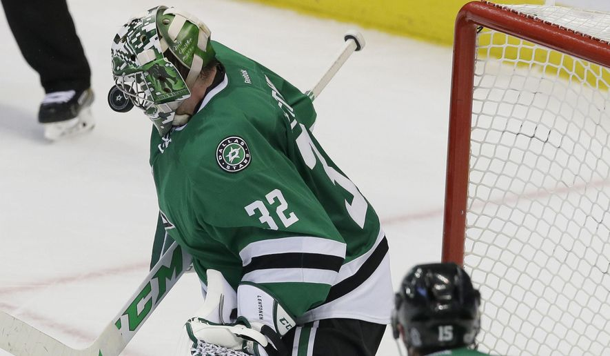 Dallas Stars goalie Kari Lehtonen (32) deflects a shot with his mask as teammates defenseman Patrik Nemeth (15) looks on during the third period of an NHL hockey game against the San Jose Sharks in Dallas, Monday, March 20, 2017. The Stars won 1-0. (AP Photo/LM Otero)