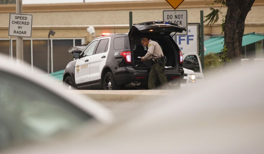 An investigation is underway after a shooting in the parking lot of the sheriff's Temple Station Monday, March 20, 2017, left a man dead inside a vehicle.  A man armed with a shotgun and a handgun opened fire on Los Angeles County sheriff's deputies Monday in the parking lot of their station, unleashing a brief gunfight that ended with the suspect likely taking his own life, authorities said. (Al Seib/Los Angeles Times via AP)