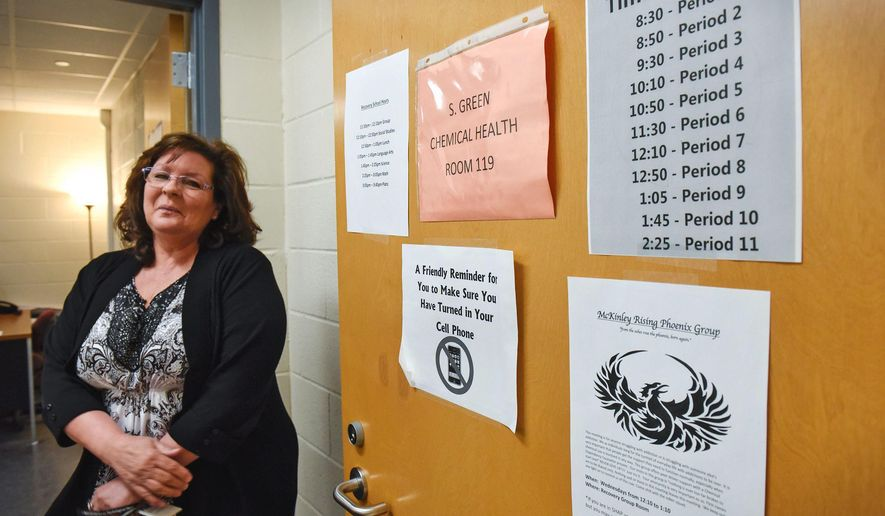 In this Friday, March 10, 2017, photo, Shelly Green, pauses near the entrance to the recovery school during an interview at McKinley Area Learning Center in Waite Park, Minn. Green a chemical health counselor, helped design McKinley Recovery School to be isolated from other parts of the main school: The sober school students start at a time different from other students, must be escorted in the hallways and stay in the classroom while teachers rotate in and out. (Dave Schwarz/St. Cloud Times via AP)