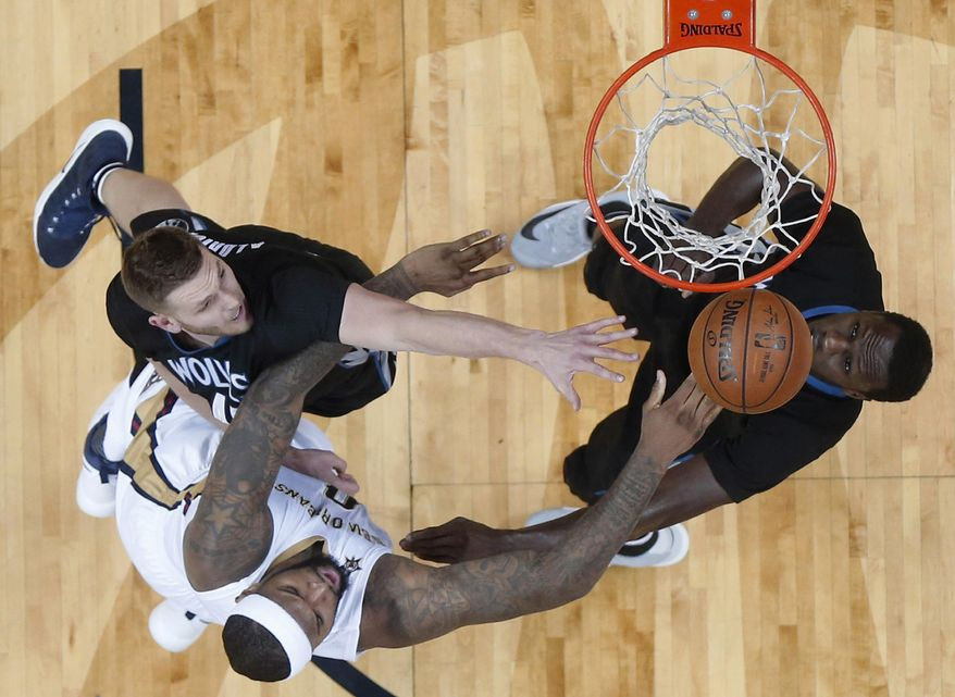 New Orleans Pelicans forward DeMarcus Cousins (0), bottom left, shoots against Minnesota Timberwolves center Cole Aldrich, top left, and forward Gorgui Dieng in the first half of an NBA basketball game in New Orleans, Sunday, March 19, 2017. (AP Photo/Gerald Herbert)