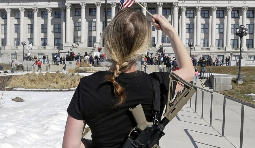 Gun right activist Siri Davidson carries her AR-15 as she walks during a march for the 2nd Amendment at the Utah State Capitol in Salt Lake City on March 2, 2013. (Associated Press) **FILE**