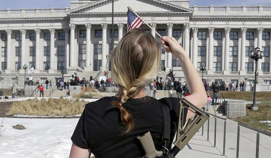 FILE - In this March 2, 2013, file photo, gun right activist Siri Davidson, carries her AR-15 as she walks during a march for the 2nd Amendment at the Utah State Capitol in Salt Lake City. Legislators have sent Utah Gov. Gary Herbert a handful of gun bills that tighten and loosen oversight on firearms. One bill would allow 18 to 20 year-olds to carry concealed weapons, despite concern from some lawmakers. (AP Photo/Rick Bowmer, File)