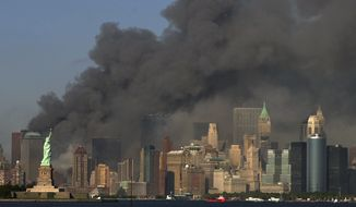 FILE- In this Tuesday, Sept. 11, 2001 file photo, thick smoke billows into the sky from the area behind the Statue of Liberty, lower left, where the World Trade Center towers stood. A bill passed by Congress allowing the families of 9/11 victims to sue the Saudi government has reinforced to some in the Arab world a long-held view that the U.S. only demands justice for its own victims of terrorism, despite decades of controversial U.S. interventions around the world. (AP Photo/Daniel Hulshizer, File)