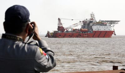 """A Myanmar police officer takes a photo of a Malaysian ship arriving at Thilawa port in Yangon, Myanmar, Thursday, Feb. 9, 2017. The """"Food Flotilla for Myanmar"""" carrying 2,300 tons of food and medicine to help members of Myanmar's persecuted Muslim Rohingya minority arrived in Yangon as rights groups accuse the army of mass killings, rapes and other crimes targeting the ethnic group. (AP Photo/Thein Zaw)"""