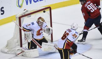 Calgary Flames goalie Brian Elliott (1) lets in a goal scored by Washington Capitals left wing Alex Ovechkin in front of left wing Marcus Johansson (90) and Calgary Flames defenseman Michael Stone (26) during the third period of an NHL hockey game, Tuesday, March 21, 2017, in Washington. (AP Photo/Molly Riley)