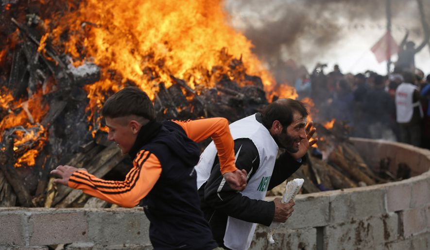 Men run in front of a bonfire during the Newroz celebration, in Diyarbakir, southeastern Turkey, Tuesday, March 21, 2017. Thousands celebrated the Newroz festival in Istanbul and in Diyarbakir, a mainly Kurdish city in a region where Kurdish militants regularly clash with government forces. In Turkey, the spring festival traditionally serves as an occasion to demand more rights for the Kurdish minority.(AP Photo/Lefteris Pitarakis)