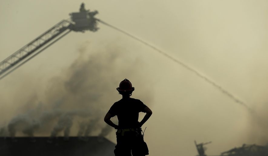 A firefighter watches from the scene of an apartment complex fire as firefighters douse fires at nearby homes Monday, March 20, 2017, in Overland Park, Kan. Once one roof caught fire, embers jumped from roof to roof, spreading the blaze, said Overland Park Fire Department spokesman Jason Rhodes. (AP Photo/Charlie Riedel)