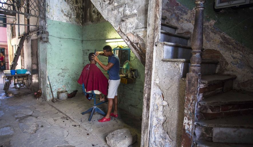 FILE - In this May 24, 2016 file photo, a barber cuts his client's hair under the staircase of his apartment building in Havana, Cuba. A rare poll of Cuban public opinion taken in late 2016 has found that most Cubans approve of normal relations with the United States and large majorities want more tourism and private business ownership. (AP Photo/Desmond Boylan, File)
