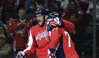 Washington Capitals right wing T.J. Oshie (77) celebrates his goal with left wing Alex Ovechkin (8) against the Calgary Flames during the second period of an NHL hockey game, Tuesday, March 21, 2017, in Washington. (AP Photo/Molly Riley)