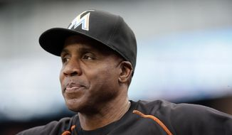 FILE - In this June 28, 2016, file photo, Miami Marlins hitting coach Barry Bonds looks from the dugout during the first inning of a baseball game against the Detroit Tigers in Detroit. Bonds has joined the San Francisco Giants front office as a special adviser, the team announced Tuesday, March 21, 2017. Bonds, who hit 762 career home runs, was fired last fall as the hitting coach for the Marlins after one season. (AP Photo/Carlos Osorio, File)