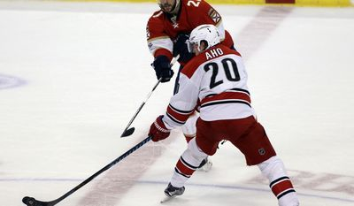 Carolina Carolina Hurricanes' Sebastian Aho (20), of Finland, and Florida Panthers' Vincent Trocheck (21) battle for the puck during the second period of an NHL hockey game, Tuesday, March 21, 2017, in Sunrise, Fla. (AP Photo/Luis M. Alvarez)