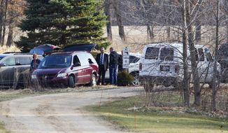 In this Monday, March 20, 2017 photo, authorities respond to a home in Courtland Township, Mich. Authorities said they believe David Applegate killed his mother, Gloria Launiere, at the home before killing himself. (Cory Morse/The Grand Rapids Press via AP)