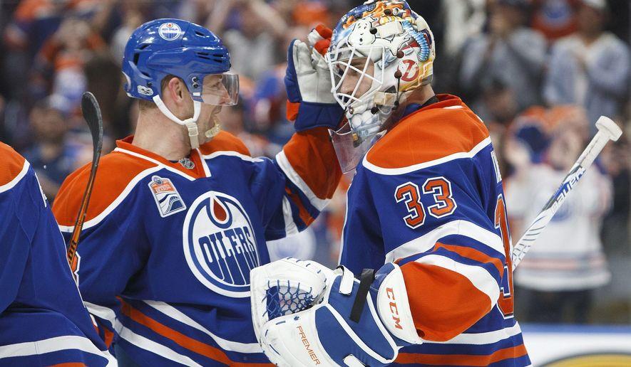 Edmonton Oilers' Matt Hendricks (23) congratulates goaltender Cam Talbot (33) after defeating the Los Angeles Kings during an NHL hockey game in Edmonton, Alberta, Monday, March 20, 2017. (Codie McLachlan/The Canadian Press via AP)