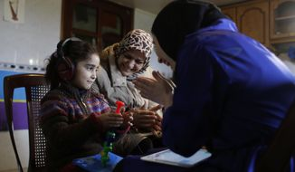 """In this Sunday, March 12, 2017 photo, Syrian refugees Aya al-Souqi, left, smiles as receiving her first hearing test by Zaineb Abdulla, right, the Vice President of """"Deaf Planet Soul"""" Chicago hearing charity at Joub Jannine village in the Bekaa valley, east Lebanon, Sunday, Sunday, March 12, 2017. The proudly named """"Deaf Planet Soul"""" Chicago hearing charity is bringing smiles to hard of hearing Syrian children and their parents in Lebanon on a two-week long mission to treat hearing loss. It is, for many of their young patients, the first time they sit with audiologists and therapists for formal treatment. (AP Photo/Hassan Ammar)"""