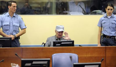 In this Friday, June 3, 2011, image former Bosnian Serb Gen. Ratko Mladic salutes as he sits between security guards in the court room during his initial appearance at the U.N.'s Yugoslav war crimes tribunal in The Hague, Netherlands. Lawyers for former Bosnian Serb military chief Gen. Ratko Mladic say he is seriously ill and could die if he is not provisionally released from custody for treatment while he awaits verdicts in his United Nations trial. (AP Photo/Martin Meissner, Pool)