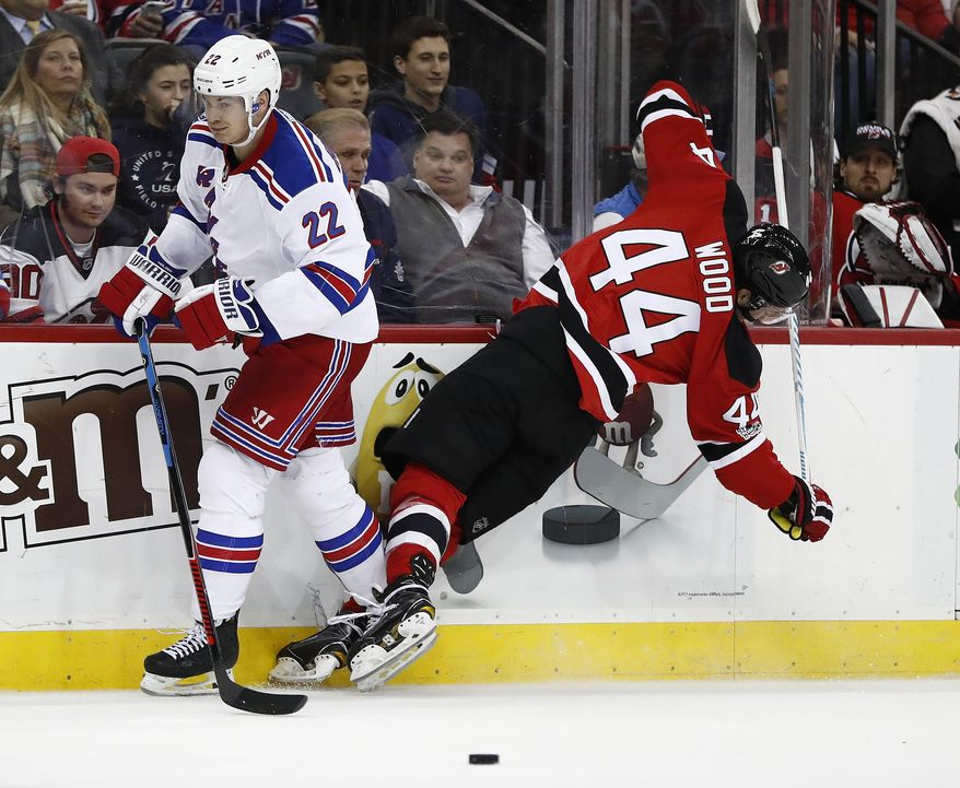 New Jersey Devils left wing Miles Wood (44) hits the boards after being checked by New York Rangers defenseman Nick Holden (22) during the second period of an NHL hockey game, Tuesday, March 21, 2017, in Newark, N.J. (AP Photo/Julio Cortez)