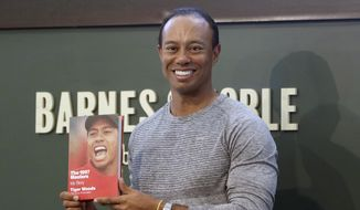 Golfer Tiger Woods holds up a copy of his new book at a book signing in New York, Monday, March 20, 2017. (AP Photo/Seth Wenig)