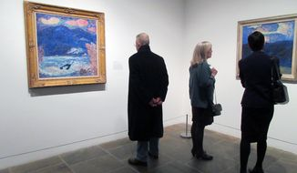 """This March 20, 2017 photo shows visitors looking at paintings from the """"Marsden Hartley's Maine"""" show at The Met Breuer Museum in New York. Hartley was a native of Maine and the exhibition showcases his landscapes and portraits of Maine. Maine's tourism agency has created itineraries that match the artwork for travelers who'd like to visit the places depicted in the paintings. (AP Photo/Beth J. Harpaz)"""