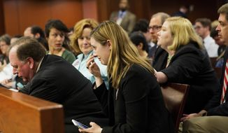 Grace Starling, center, a law student at Georgia State University, activist and sexual assault victim, wipes away tears after her father Kenneth Starling, left, testified before a Georgia Senate subcommittee on a bill overhauling colleges' disciplinary hearings on sexual violence in Atlanta, Tuesday, March 21, 2017. The subcommittee heard more than an hour of testimony Tuesday on the bill but didn't vote. Opponents say it will discourage victims from coming forward. The bill's sponsor, Georgia Rep. Earl Ehrhart, R-Powder Springs, says it will protect the rights of accused students. (AP Photo/David Goldman)