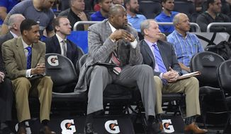 Charlotte Hornets assistant coach Patrick Ewing, center, watches from the bench during the second half of an NBA basketball game against the Orlando Magic in Orlando, Fla., Wednesday, March 22, 2017. The Hornets won 109-102. (AP Photo/Phelan M. Ebenhack)