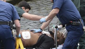 "An attacker is treated by emergency services outside the Houses of Parliament London, Wednesday, March 22, 2017.  London police say they are treating a gun and knife incident at Britain's Parliament ""as a terrorist incident until we know otherwise."" The Metropolitan Police says in a statement that the incident is ongoing. It is urging people to stay away from the area. Officials say a man with a knife attacked a police officer at Parliament and was shot by officers. Nearby, witnesses say a vehicle struck several people on the Westminster Bridge.  (Stefan Rousseau/PA via AP)."