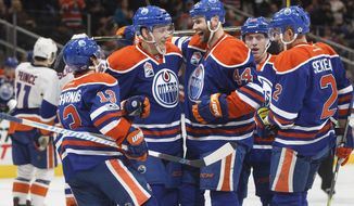 FILE - In this March 7, 2017, file photo, Edmonton Oilers' David Desharnais (13), Matthew Benning (83), Zack Kassian (44), Drake Caggiula (36) and Andrej Sekera (2) celebrate a goal against the New York Islanders during the second period of an NHL hockey game in Edmonton, Alberta. Alberta is home to two of the hottest teams in the NHL at playoff time (the Flames and Oilers), and it's been 11 years since they were in it at the same time.  (Jason Franson/The Canadian Press via AP, File)