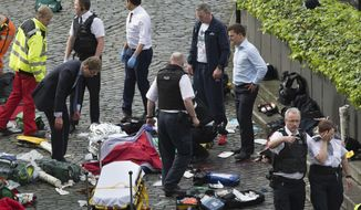 """Conservative MP Tobias Ellwood, left, stands amongst the emergency services at the scene outside the Palace of Westminster, London, Wednesday, March 22, 2017.  London police say they are treating a gun and knife incident at Britain's Parliament """"as a terrorist incident until we know otherwise."""" The Metropolitan Police says in a statement that the incident is ongoing. It is urging people to stay away from the area. Officials say a man with a knife attacked a police officer at Parliament and was shot by officers. Nearby, witnesses say a vehicle struck several people on the Westminster Bridge.  (Stefan Rousseau/PA via AP)."""