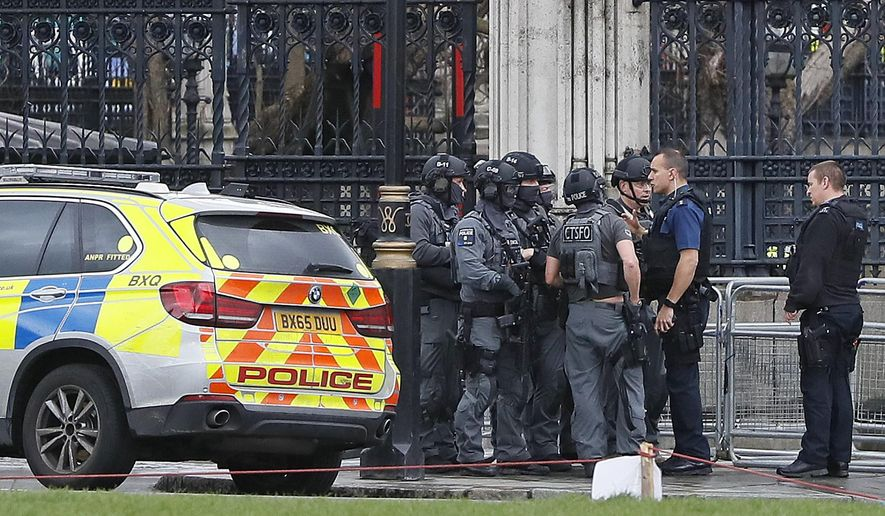 "Armed police officers gather outside of the Houses of Parliament in London, Wednesday, March 23, 2017 after the House of Commons sitting was suspended as witnesses reported sounds like gunfire outside. The leader of Britain's House of Commons says a man has been shot by police at Parliament. David Liddington also said there were ""reports of further violent incidents in the vicinity.""(AP Photo/Kirsty Wigglesworth)"