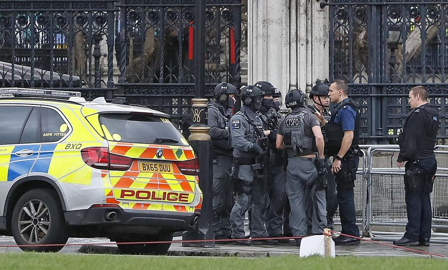 """Armed police officers gather outside of the Houses of Parliament in London, Wednesday, March 23, 2017 after the House of Commons sitting was suspended as witnesses reported sounds like gunfire outside. The leader of Britain's House of Commons says a man has been shot by police at Parliament. David Liddington also said there were """"reports of further violent incidents in the vicinity.""""(AP Photo/Kirsty Wigglesworth)"""