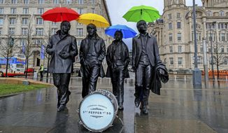 "Umbrellas are placed over the statute of the Beatles, during a photocall, on Liverpool's waterfront, in Liverpool, England, Wednesday, March 22, 2017. The city of Liverpool is getting set to celebrate the half-centenary of ""Sgt. Pepper's Lonely Hearts Club Band,"" one of the most influential albums by local heroes The Beatles. (Peter Byrne/PA via AP)"